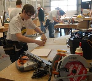 Performance techno-franco 2012. un jeune étudiant travail avec une scie méchanique dans un atelier.